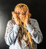 Man eating spaghetti with tomato sauce in head. Mad man eating spaghetti with tomato sauce in head Royalty Free Stock Images