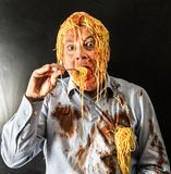 Man eating spaghetti with tomato sauce in head. Mad man eating spaghetti with tomato sauce in head Royalty Free Stock Photography