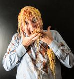Man eating spaghetti with tomato sauce in head. Mad man eating spaghetti with tomato sauce in head Royalty Free Stock Image