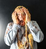 Man eating spaghetti with tomato sauce in head. Mad man eating spaghetti with tomato sauce in head Royalty Free Stock Photo