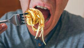 Man eating spaghetti with worms. Closeup of man eating spaghetti with crispy worms stock photos
