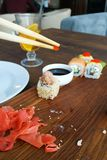 Man is eating sushi in the black plate on a wooden table, Rolls close-up royalty free stock images