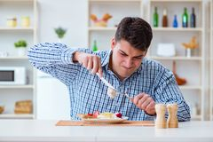 The man eating tasteless food at home for lunch Stock Image