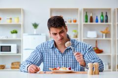 The man eating tasteless food at home for lunch Stock Photography