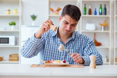 The man eating tasteless food at home for lunch Royalty Free Stock Photography