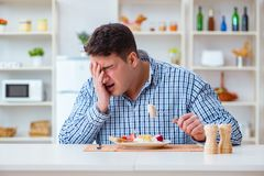 The man eating tasteless food at home for lunch Royalty Free Stock Images
