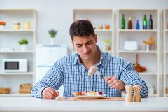The man eating tasteless food at home for lunch Royalty Free Stock Photos