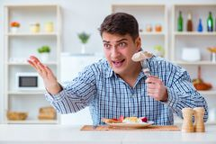 The man eating tasteless food at home for lunch Royalty Free Stock Image