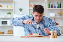 The man eating tasteless food at home for lunch Stock Photo