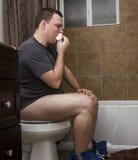 Man eating toilet paper. Stock Image