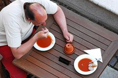 Man eating tomato soup Royalty Free Stock Photo