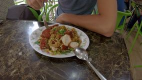 Man eating a traditional Malaysian and Indonesian food - mie goreng wrapped in a fried egg. Travel to Malaysia and. Indonesia concept stock footage
