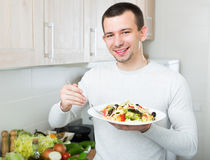 Free Man Eating Vegetable Salad In Kitchen Royalty Free Stock Photo - 77473245