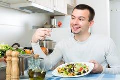 Man eating vegetable salad in kitchen Stock Photos