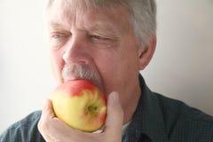 Man eats apple Stock Photos