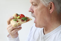 Man eats BLT pizza profile view Royalty Free Stock Images