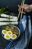A man eats buckwheat soba noodles with sauce and side dishes in broth. Japanese food. Asian cuisine. Black wooden background. Side royalty free stock image