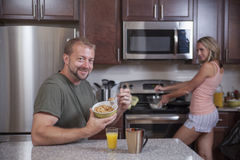 Man eats cereal while lady makes breakfast. Man eats cereal while waiting for his wife to finish cooking breakfast stock photos