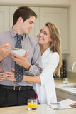 Man eats cereal while partner is embracing him Stock Photo
