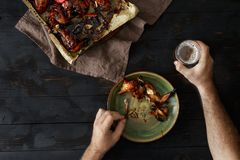 Man eats chicken wings with beer, top view. Dinner table. Man eats chicken wings with beer on dark wooden table, top view. Dinner table concept Royalty Free Stock Photos