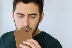 Man eats chocolate with great pleasure stock photography