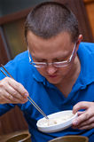 Man eats with chopsticks. White caucasian man eating with chopsticks royalty free stock photo