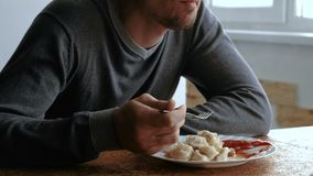 Man eats dumplings with a fork, putting them into tomato sauce in the kitchen stock footage