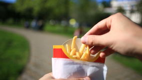 A man eats fast food on the street. He carries a French fries and eats it. Against the background of a blurry city stock video footage