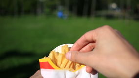 A man eats fast food on the street. He carries a French fries and eats it. Against the background of a blurry city stock footage