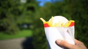 A man eats fast food on the street. He carries a French fries and eats it. Against the background of a blurry city stock video