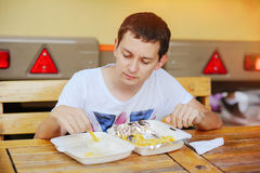 Man eats French fries. Road fast food Royalty Free Stock Photos