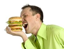 Man eats hamburger. Hungry man is eating huge hamburger Stock Photo