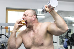 Man eats a hamburger with meat and cheese in the gym Stock Photos
