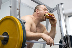 Man eats a hamburger with meat and cheese in the gym Royalty Free Stock Images