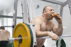 Man eats a hamburger with meat and cheese in the gym Royalty Free Stock Photography