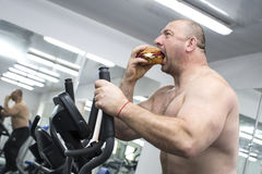 Man eats a hamburger with meat and cheese in the gym Stock Image