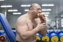 Man eats a hamburger with meat and cheese in the gym Royalty Free Stock Photos