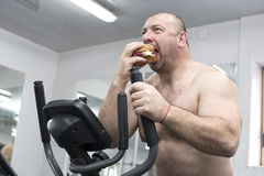 Man eats a hamburger with meat and cheese in the gym Royalty Free Stock Photo