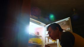 Man eats hunger and gluttony from the refrigerator at night. man looks into the fridge at night. gluttony lifestyle