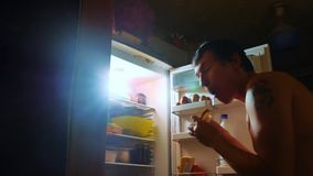 Man eats hunger and gluttony from the refrigerator at night. man looks into the fridge at night. gluttony overweight