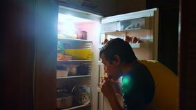 Man eats hunger and gluttony from the refrigerator at night. man looks into the fridge at night lifestyle. gluttony