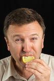 A man eats a lemon Stock Image