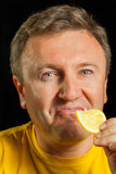 A man eats a lemon Stock Photo