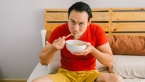 Man eats noodles. Stock Image