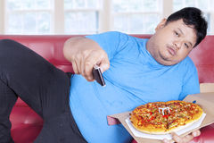 Man eats pizza while watching tv 2 Stock Photo