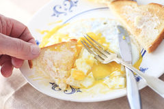 Man eats runny eggs and toast POV Royalty Free Stock Images