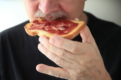 Man eats slice of toast with jam Royalty Free Stock Image
