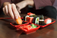 Man eats sushi roll with hands Stock Image
