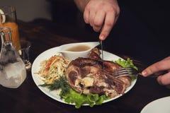 Man eats tasty dish of pork shank Stock Images