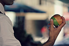A man eats a two-toned apple sits at an outdoor bar Royalty Free Stock Photo
